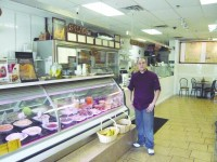 Diego Sarmiento stands proudly in his restaurant.