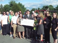 Gipson, Alvarez, Tobin hold a $100,000 check that will go to a new playground at Kent Elementary.