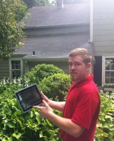 """Kevin Singleton from Franzoso Contracting demonstrates the Roof Shampoo process on his iPad.  In the background is The Home Guru's badly stained roof with mold and lichen, """"before."""""""