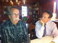 """Bob Buchanan, psychic medium, left, in a trance-like state, in the kitchen of The Home Guru, """"reading"""" the visiting spirits."""