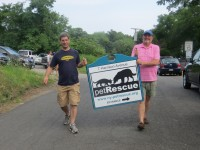 Volunteers carry the new Pet Rescue sign out to Harrison Avenue on Sunday during the open house for the new facility