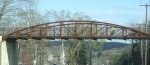 A bicyclist glides across the bike path bridge that spans over Route 6.