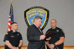 Sheriff Smith reading the award citations aloud as he is flanked by Deputy Blessing on the viewer's left and Deputy Hunsberger on the right.