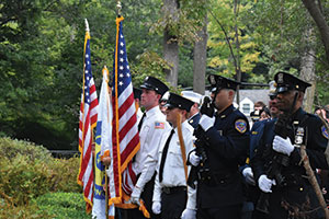Service men and police officers holding American flags at a 9/11 memorial ceremony